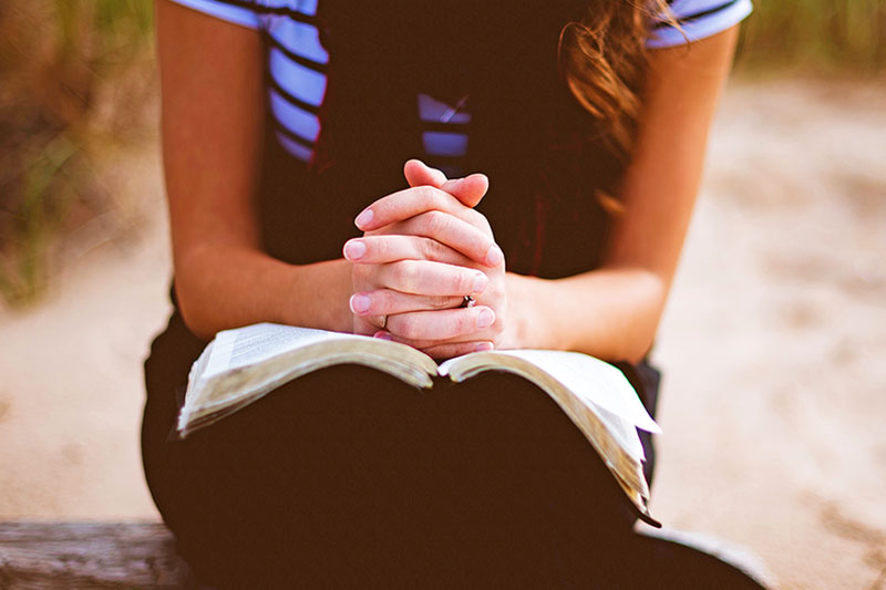 Hands Crossed in prayer over a bible